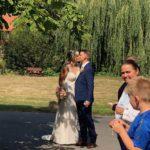 Brautpaar küsst sich vor der Kirche